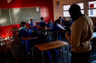 A pupil at the Winnie Mandela Secondary School raises her hand during roll call as classes resume in the Tembisa township, Ekurhuleni, on June 8, 2020. - Grade 7 and grade 12 pupils in South Africa began returning to classrooms on June 8, 2020  after two and a half months of home-schooling to limit the spread of the COVID-19 coronavirus. (Photo by Michele Spatari / AFP) (Photo by MICHELE SPATARI/AFP via Getty Images)