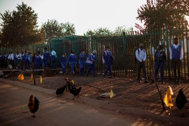 Pupils at the Winnie Mandela Secondary School wait in line outside the school premises before classes resume in the Tembisa township, Ekurhuleni, on June 8, 2020. - Grade 7 and grade 12 pupils in South Africa began returning to classrooms on June 8, 2020  after two and a half months of home-schooling to limit the spread of the COVID-19 coronavirus. (Photo by Michele Spatari / AFP) (Photo by MICHELE SPATARI/AFP via Getty Images)