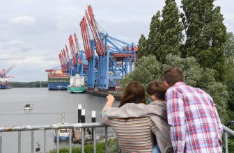 HAMBURG, GERMANY - JUNE 07: A family look  at the HMM Algeciras, currently the world's largest container ship, arrives on its maiden voyage on June 07, 2020 in Hamburg, Germany. The ship is 399.9 meters long and 61 meters wide, and has a nominal capacity to transport 23,964 containers. It is the first in a series of twelve ships in the 24,000 TEU class and was built in South Korea. (Photo by Stuart Franklin/Getty Images)