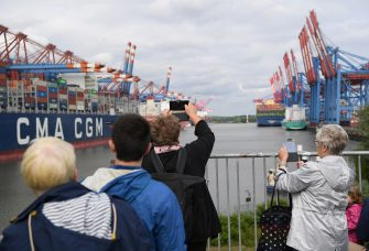 HAMBURG, GERMANY - JUNE 07: People watch the HMM Algeciras, currently the world's largest container ship, arrives on its maiden voyage on June 07, 2020 in Hamburg, Germany. The ship is 399.9 meters long and 61 meters wide, and has a nominal capacity to transport 23,964 containers. It is the first in a series of twelve ships in the 24,000 TEU class and was built in South Korea. (Photo by Stuart Franklin/Getty Images)