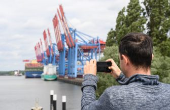 HAMBURG, GERMANY - JUNE 07: A person takes a picture of the HMM Algeciras, currently the world's largest container ship, arrives on its maiden voyage on June 07, 2020 in Hamburg, Germany. The ship is 399.9 meters long and 61 meters wide, and has a nominal capacity to transport 23,964 containers. It is the first in a series of twelve ships in the 24,000 TEU class and was built in South Korea. (Photo by Stuart Franklin/Getty Images)