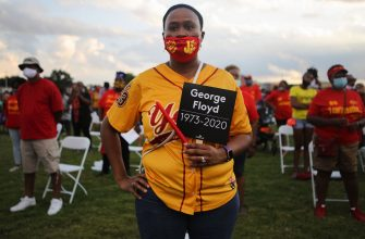 HOUSTON, TEXAS - JUNE 08:  School alumni wear their school colors as they participate in a vigil honoring George Floyd on the football field of Jack Yates High School on June 8, 2020 in Houston, Texas. George Floyd, who played football for Yates High School, died on May 25th when he was in Minneapolis police custody, sparking nationwide protests. A white police officer, Derek Chauvin, has been charged with second-degree murder, with the three other officers involved facing other charges. (Photo by Mario Tama/Getty Images)
