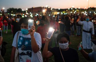 TOPSHOT - Visitors hold their lit phones as they pay their respects to George Floyd during a candlelight vigil at Jack Yates High School in Houston, Texas on June 8, 2020. - George Floyd, the 46-year-old African American whose killing by a white police officer transformed him into a global icon of the struggle against racism and police brutality, will be laid to rest on June 9 in Houston, the city where he grew up. (Photo by ANDREW CABALLERO-REYNOLDS / AFP) (Photo by ANDREW CABALLERO-REYNOLDS/AFP via Getty Images)