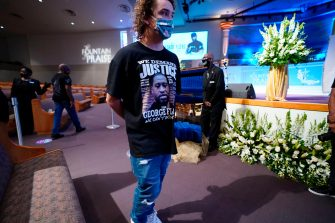 Mourners pass by the casket of George Floyd during a public visitation for Floyd at the Fountain of Praise church Monday, June 8, 2020, in Houston. (Photo by David J. Phillip / POOL / AFP) (Photo by DAVID J. PHILLIP/POOL/AFP via Getty Images)