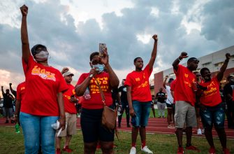 Visitors raise their fists as they pay their respects to George Floyd during a candlelight vigil at Jack Yates High School in Houston, Texas on June 8, 2020. - George Floyd, the 46-year-old African American whose killing by a white police officer transformed him into a global icon of the struggle against racism and police brutality, will be laid to rest on June 9 in Houston, the city where he grew up. (Photo by ANDREW CABALLERO-REYNOLDS / AFP) (Photo by ANDREW CABALLERO-REYNOLDS/AFP via Getty Images)