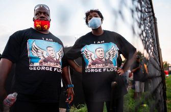 Visitors pay their respects to George Floyd during a candlelight vigil at Jack Yates High School in Houston, Texas on June 8, 2020. - George Floyd, the 46-year-old African American whose killing by a white police officer transformed him into a global icon of the struggle against racism and police brutality, will be laid to rest on June 9 in Houston, the city where he grew up. (Photo by ANDREW CABALLERO-REYNOLDS / AFP) (Photo by ANDREW CABALLERO-REYNOLDS/AFP via Getty Images)