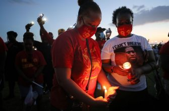 HOUSTON, TEXAS - JUNE 08:  School alumni and residents participate in a candlelight vigil honoring George Floyd on the football field of Jack Yates High School on June 8, 2020 in Houston, Texas. George Floyd, who played football for Yates High School, died on May 25th when he was in Minneapolis police custody, sparking nationwide protests. A white police officer, Derek Chauvin, has been charged with second-degree murder, with the three other officers involved facing other charges. (Photo by Mario Tama/Getty Images)
