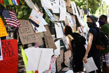 People look at posters and placards on the security fence on the north side of Lafayette Square, near the White House, in Washington, DC on June 8, 2020. - On May 25, 2020, Floyd, a 46-year-old black man suspected of passing a counterfeit $20 bill, died in Minneapolis after Derek Chauvin, a white police officer, pressed his knee to Floyd's neck for almost nine minutes. (Photo by MANDEL NGAN / AFP) (Photo by MANDEL NGAN/AFP via Getty Images)