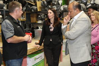 TAURANGA, NEW ZEALAND - JUNE 09: Prime Minister Jacinda Ardern (C), MP Willie Jackson (R) meets with Alister Baird from New Zealand Homes Solutions (L) who employed apprentice Jake Alder under the Mana in Mahi scheme on June 09, 2020 in Tauranga, New Zealand. COVID-19 restrictions were lifted from midnight as New Zealand moved to COVID-19 Alert Level 1 as the government confirmed there are zero active cases in the country. The lifting of restrictions under Alert Level 1 will see life mostly return to normal in New Zealand, however strict border measures will remain with mandatory isolation and quarantine for any overseas arrivals. New Zealanders are also being asked to keep diaries in the event of a second wave of infections. (Photo by Michael Bradley/Getty Images)