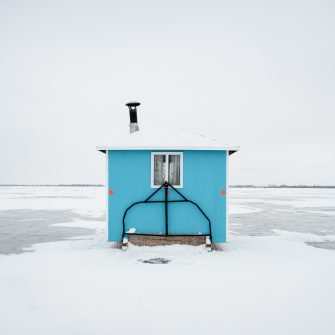 Winters in Manitoba, Canada, are long and often bitterly cold. When the temperature drops, and thick ice forms, lakes and rivers in the province play host to some amazing folk architecture in the form of ice fishing huts. These huts, shacks or permies (as they are called in Manitoba) must be transportable, protect their occupants from the elements and allow access to the ice below for fishing. Once these requirements have been met, the owners are free to express their personalities in the shape, structure and decoration of their huts - they are large or small, decorated or plain, luxurious or utilitarian and everything in between. I captured these images on Lake Winnipeg in December 2019. My hope for this series, which is a continuation of work I started in 2018, is to showcase the quirky charm of these huts by presenting a select few in a typology. The typology - showing the huts framed in the same, minimalist style and in the same lighting - allows the viewer to notice similarities in function and uniqueness in form, as well as to display these utilitarian structures as beautiful works of art.