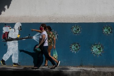 RIO DE JANEIRO, BRAZIL - JUNE 08: People wearing face masks walk past a wall with a graffiti depicting a cleaner in protective gear spraying viruses with the face of President Jair Bolsonaro in Estacio neighborhood amidst the coronavirus (COVID-19) pandemic on June 8, 2020 in Rio de Janeiro, Brazil. (Photo by Bruna Prado/Getty Images)