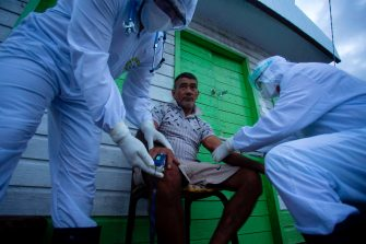 Health workers from the city of Melgaco check a resident of a small riverside community in the southwest of Marajo Island, state of Para, Brazil, on June 9, 2020, amid concern over the spread of the COVID-19 coronavirus. (Photo by TARSO SARRAF / AFP) (Photo by TARSO SARRAF/AFP via Getty Images)