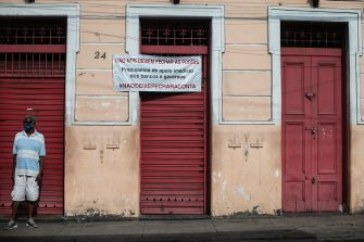 """RIO DE JANEIRO, BRAZIL - JUNE 09: A man wearing a face mask stands in front of a shuttered and closed traditional bar in the Santa Teresa neighborhood with a banner that reads in Portuguese """"Don't let us close the doors. We need immediate support from banks and the government. #DontLetTheTabClose"""" amidst the coronavirus (COVID-19) pandemic on June 9, 2020 in Rio de Janeiro, Brazil. Many businesses in the city of Rio de Janeiro went bankrupt and some commercial spaces are either for sale or for lease during the coronavirus (COVID-19) pandemic. (Photo by Bruna Prado/Getty Images)"""