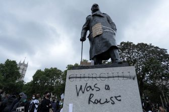 """The statue of former British prime minister Winston Churchill is seen defaced, with the words (Churchill) """"was a racist"""" written on it's base in Parliament Square, central London after a demonstration outside the US Embassy, on June 7, 2020, organised to show solidarity with the Black Lives Matter movement in the wake of the killing of George Floyd, an unarmed black man who died after a police officer knelt on his neck in Minneapolis. - Taking a knee, banging drums and ignoring social distancing measures, outraged protesters from Sydney to London on Saturday kicked off a weekend of global rallies against racism and police brutality. (Photo by ISABEL INFANTES / AFP) (Photo by ISABEL INFANTES/AFP via Getty Images)"""
