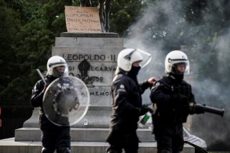 Riot police protect the King Leopold II of Belgium statue during an anti-racism protest, in Brussels, on June 7, 2020, as part of a weekend of 'Black Lives Matter' worldwide protests against racism and police brutality in the wake of the death of George Floyd, an unarmed black man killed while apprehended by police in Minneapolis, US. (Photo by Kenzo TRIBOUILLARD / AFP) (Photo by KENZO TRIBOUILLARD/AFP via Getty Images)