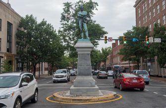 """A bronze statue, titled the Confederate Soldier is viewed in downtown Alexandria, Virginia, on August 14, 2017. He stands in the middle of the street, his back to the nation's capital as he gazes southwards towards the bloody battlefields of the Civil War. Erected nearly 130 years ago, the bronze statue of an unarmed Confederate soldier sits at a busy intersection in Alexandria, Virginia, just across the Potomac River from Washington,DC.The Alexandria statue, known as """"Appomattox,"""" is one of hundreds of similar monuments across the American South honoring the Confederate dead.Debate over what to do with these controversial symbols of the Confederacy has been simmering for years and is likely to intensify after boiling over into bloodshed at the weekend.  / AFP PHOTO / Paul J. Richards / TO GO WITH AFP STORY BY CHRIS LEFKOW- """"Pressure builds to remove Confederate statues following clashes over plans to pull down a monument to rebel commander Robert E. Lee in a Virginia city""""        (Photo credit should read PAUL J. RICHARDS/AFP via Getty Images)"""