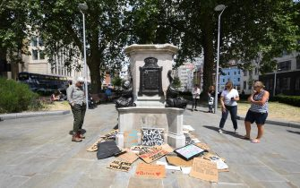 epa08475041 People look over the plinth of the Edward Colston statue in Bristol, Britain, 09 June, 2020. Merchant slave trader Edward Colston statue was pulled down during a Black Lives Matter protest 07 June. Protesters in across the UK continue to demonstrate in the wake of the death in police custody of George Floyd in the United States.  EPA/ANDY RAIN