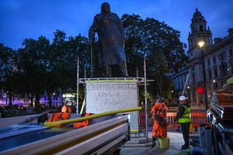 "LONDON, ENGLAND - JUNE 11: Workers erect a protective barrier around the statue of Winston Churchill in Parliament Square in anticipation of protests tomorrow on June 11, 2020 in London, England. Outside the Houses of Parliament, the statue of former Prime Minister Winston Churchill was spray-painted with the words ""was a racist"" amid anti-racism protests over the weekend. In Bristol, protesters toppled a statue of Edward Colston, a 17th-century slave-trader, and tossed it into the harbor. (Photo by Peter Summers/Getty Images)"