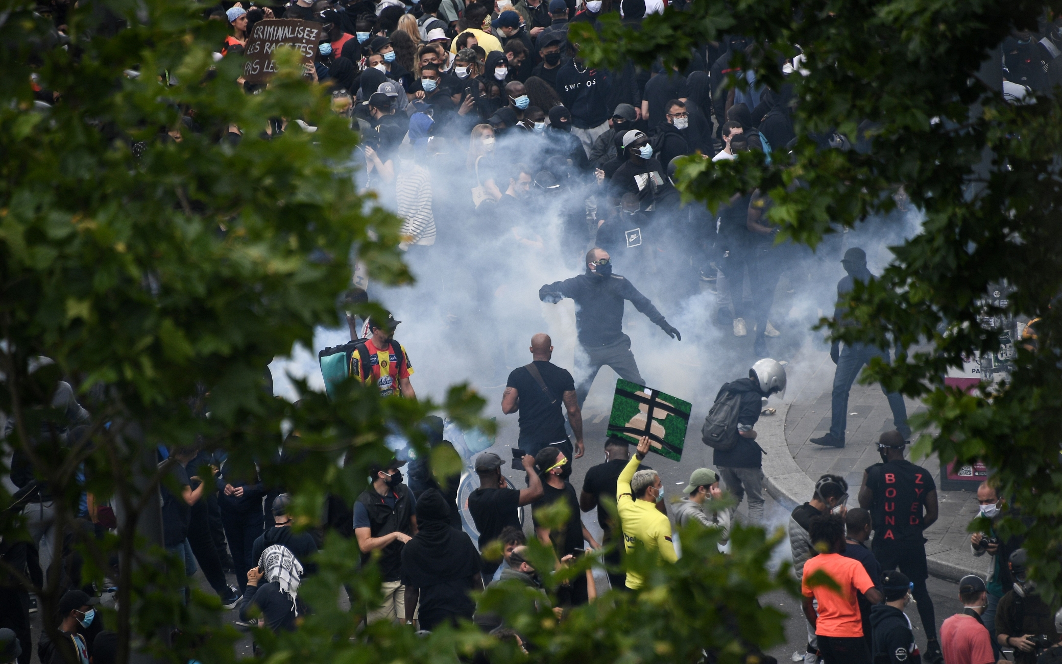 People throw back tear gas canisters at French riot police forces during a rally as part of the 'Black Lives Matter' worldwide protests against racism and police brutality, on Place de la Republique in Paris on June 13, 2020. - A wave of global protests in the wake of US George Floyd's fatal arrest magnified attention on the 2016 death in French police custody of Adama Traore, a 24-year-old black man, and renewed controversy over claims of racism and brutality within the force. (Photo by Anne-Christine POUJOULAT / AFP) (Photo by ANNE-CHRISTINE POUJOULAT/AFP via Getty Images)