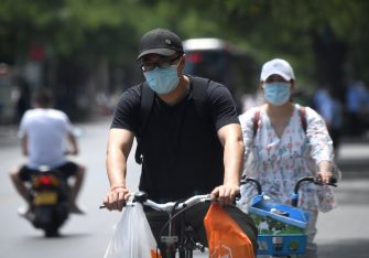 People wearing face masks ride their bike on a street along a residential area under lockdown near Yuquan East Market in Beijing on June 15, 2020. - China locks down ten more Beijing neighbourhoods over virus cluster. (Photo by Noel Celis / AFP) (Photo by NOEL CELIS/AFP via Getty Images)