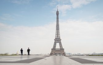 PARIS, FRANCE - MARCH 17: Police officers patrol near the Eiffel Tower during a government enforced quarantine on March 17, 2020 in Paris, France. On March 17, 2020 France imposed a nationwide lockdown to control the spread of COVID-19. (Photo by Veronique de Viguerie/Getty Images)