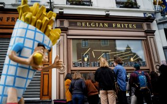 People stand in line in front of a French fries vendor near the Grand Place in central Brussels, on March 14, 2020, amid the outbreak of COVID-19, caused by the novel coronavirus. - Since the beginning of the outbreak, 559 cases of COVID-19 have been recorded in Belgium, according to an AFP tally compiled on March 13, 2020. (Photo by Kenzo TRIBOUILLARD / AFP) (Photo by KENZO TRIBOUILLARD/AFP via Getty Images)