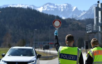 FUSSEN, GERMANY - APRIL 05: German police officers stop a car at a checkpoint at the border to Austria, where crossings have been severely restricted in an effort to rein in the spread of the coronavirus, on April 5, 2020 near Fussen, Germany. Public life in Bavaria remains heavily curtailed with outings limited to essentials as both the state of Bavaria and federal Germany seek to stem the spread of the virus. Nationwide confirmed cases of infection have reached 96,000 and 1,444 people have died. (Photo by Andreas Gebert/Getty Images)