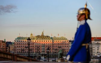 A palace guard stands in front of the Royal Palace while the sun sinks over Grand Hotel in downtown Stockholm, Sweden on September 3, 2013, on the eve of the two-day visit by US President Barack Obama.   AFP PHOTO / SCANPIX SWEDEN / HENRIK MONTGOMERY +++ SWEDEN OUT        (Photo credit should read HENRIK MONTGOMERY/AFP via Getty Images)