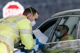 MATREI AM BRENNER, AUSTRIA - MARCH 11: A man in protective gear gives a fact sheet of the coronavirus to a driver of a car arriving from Italy at the Brenner Pass border crossing on March 11, 2020 near Matrei am Brenner, Austria. Austrian Chancellor Sebastian Kurz yesterday announced Austria is turning away people arriving from Italy, except those with a doctor's certificate, in a measure to prevent the spread of the coronavirus. Freight is still being allowed in and any Austrians arriving will also be admitted but will need to submit to quarantine. The Italian government yesterday imposed nationwide measures in a bid to slow the spread of the virus, which has topped 9,100 confirmed cases in Italy. (Photo by Jan Hetfleisch/Getty Images)