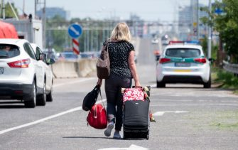 A woman walks with her luggage while crossing the Bratislava-Berg border crossing between Austria and Slovakia during the coronavirus COVID-19 pandemic on June 4, 2020. - Austria has re-opened its borders to all its neighbors except Italy, although the neighboring countries did not reciprocate reopening of frontier crossings, testing the patience of some motorists and other travelers. (Photo by JOE KLAMAR / AFP) (Photo by JOE KLAMAR/AFP via Getty Images)