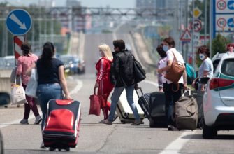 Women walk with their luggage while crossing the Bratislava-Berg border crossing between Austria and Slovakia during the coronavirus COVID-19 pandemic on June 4, 2020. - Austria has re-opened its borders to all its neighbors except Italy, although the neighboring countries did not reciprocate reopening of frontier crossings, testing the patience of some motorists and other travelers. (Photo by JOE KLAMAR / AFP) (Photo by JOE KLAMAR/AFP via Getty Images)