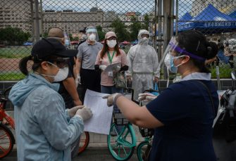 BEIJING, CHINA - JUNE 15: A Chinese epidemic control worker wears a protective suit and mask as he and volunteers direct and register people at a site where authorities were performing nucleic acid tests for COVID-19 on citizens who have had contact with the the Xinfadi Wholesale Market or someone who has, at an outdoor sports center June 15, 2020 in Beijing, China. Authorities are trying to contain the outbreak linked to the Xinfadi wholesale food market, Beijing's biggest supplier of produce and meat. Several neighborhoods have been locked down and at least two other food markets were closed, as tens of thousands of people are being urged to get tested for COVID-19 at sites set up around the city. The outbreak has triggered fears of a second wave of infection after 56 straight days with no domestically transmitted cases in the capital. More than 8,000 vendors and staff at Xinfadi have already been tested, according to city officials, who are using contact tracing to reach an estimated 200,000 people who have visited the market since May 30. (Photo by Kevin Frayer/Getty Images)