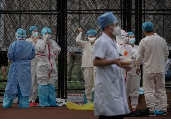 BEIJING, CHINA - JUNE 15: Chinese epidemic control workers wear protective suits and masks as they gather before resuming their duties performing nucleic acid tests for COVID-19 on citizens who have had contact with the the Xinfadi Wholesale Market or someone who has on at an outdoor sports center June 15, 2020 in Beijing, China. Authorities are trying to contain the outbreak linked to the Xinfadi wholesale food market, Beijing's biggest supplier of produce and meat. Several neighborhoods have been locked down and at least two other food markets were closed, as tens of thousands of people are being urged to get tested for COVID-19 at sites set up around the city. The outbreak has triggered fears of a second wave of infection after 56 straight days with no domestically transmitted cases in the capital. More than 8,000 vendors and staff at Xinfadi have already been tested, according to city officials, who are using contact tracing to reach an estimated 200,000 people who have visited the market since May 30. (Photo by Kevin Frayer/Getty Images)