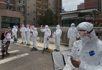 BEIJING, CHINA - JUNE 15: Chinese epidemic control workers wear protective suits and masks hold ups signs as a foreign woman and her child arrive to a residential compound as part of quarantine measures after arriving in China on June 15, 2020 in Beijing, China. In an effort to limit imported cases China closed its borders to non-citizens on March 28, 2020 allowing only those with special permission to enter the country. Those who do are required to complete 14 days of quarantine and week medical observation. Authorities are trying to contain the outbreak linked to the Xinfadi wholesale food market, Beijing's biggest supplier of produce and meat. Several neighborhoods have been locked down and at least two other food markets were closed, as tens of thousands of people are being urged to get tested for COVID-19 at sites set up around the city. The outbreak has triggered fears of a second wave of infection after 56 straight days with no domestically transmitted cases in the capital. More than 8,000 vendors and staff at Xinfadi have already been tested, according to city officials, who are using contact tracing to reach an estimated 200,000 people who have visited the market since May 30. (Photo by Kevin Frayer/Getty Images)