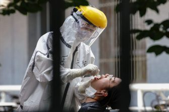 BEIJING, CHINA - JUNE 16: A nurse wearing a protective suit and mask takes a nucleic acid test for COVID-19 from a person who either visited or lives near the Xinfadi Market at a testing facility at a Sport Center on June 16, 2020 in Beijing, China. From June 11 to June 16, Beijing reported a total of 106 new confirmed cases of coronavirus (covid-19), the number of new infection has risen after no new cases for nearly two months. (Photo by Lintao Zhang/Getty Images)