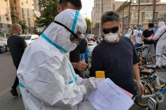 BEIJING, CHINA - JUNE 15:  (Editor's Note: Photo taken with mobile phone camera.) Citizens who visited or live near Xinfadi Market queue for a nucleic acid test at Guangan Sport Center on June 14, 2020 in Beijing, China. From June 11 to June 14, Beijing reported a total of 79 new confirmed cases of new coronary pneumonia (covid-19), the number of new infection has risen after no new cases for nearly two months.  (Photo by Lintao Zhang/Getty Images)