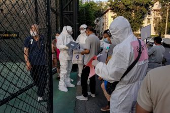 BEIJING, CHINA - JUNE 15: Chinese nurse wearing a protective suit checks the list at the entrance of citizens who visited or live near Xinfadi Market queue for a nucleic acid test at Guangan Sport Center on June 14, 2020 in Beijing, China. From June 11 to June 14, Beijing reported a total of 79 new confirmed cases of new coronary pneumonia (covid-19), the number of new infection has risen after no new cases for nearly two months.  (Photo by Lintao Zhang/Getty Images)