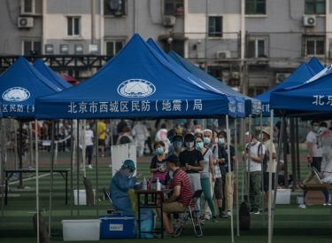 BEIJING, CHINA - JUNE 15: Citizens and Chinese epidemic control workers are seen at a site where authorities were performing nucleic acid tests for COVID-19 on citizens who have had contact with the the Xinfadi Wholesale Market or someone who has, at an outdoor sports center June 15, 2020 in Beijing, China. Authorities are trying to contain the outbreak linked to the Xinfadi wholesale food market, Beijing's biggest supplier of produce and meat. Several neighborhoods have been locked down and at least two other food markets were closed, as tens of thousands of people are being urged to get tested for COVID-19 at sites set up around the city. The outbreak has triggered fears of a second wave of infection after 56 straight days with no domestically transmitted cases in the capital. More than 8,000 vendors and staff at Xinfadi have already been tested, according to city officials, who are using contact tracing to reach an estimated 200,000 people who have visited the market since May 30. (Photo by Kevin Frayer/Getty Images)