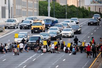 epa08487494 Protesters shut down Interstate 395, a highway that runs through the nation's capital, during a protest to demand justice for George Floyd and for racial equality, in Washington, DC, USA, 15 June 2020. Protesters kneeled on the ground and forced traffic to stop. The death of George Floyd while in police custody in Minneapolis has sparked global protests demanding policing reform.  EPA/MICHAEL REYNOLDS
