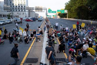 epa08487496 Protesters shut down Interstate 395, a highway that runs through the nation's capital, during a protest to demand justice for George Floyd and for racial equality, in Washington, DC, USA, 15 June 2020. Protesters kneeled on the ground and forced traffic to stop. The death of George Floyd while in police custody in Minneapolis has sparked global protests demanding policing reform.  EPA/MICHAEL REYNOLDS