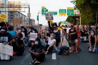 Protesters demonstrate the death of George Floyd by taking a knee to close down and block traffic on I-395 in Washington, DC, on June 15, 2020. - George Floyd's May 25 death in police custody has ignited a wave of protests for racial justice and police reform across the United States. (Photo by JIM WATSON / AFP) (Photo by JIM WATSON/AFP via Getty Images)