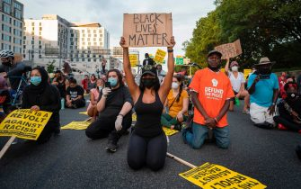 Protesters kneel and hold up signs as they demonstrate the death of George Floyd by closing down and blocking traffic on I-395 in Washington, DC, on June 15, 2020. - George Floyd's May 25 death in police custody has ignited a wave of protests for racial justice and police reform across the United States. (Photo by JIM WATSON / AFP) (Photo by JIM WATSON/AFP via Getty Images)