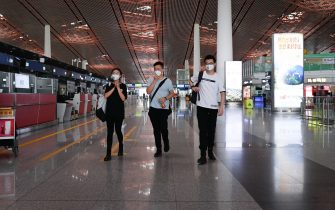 A group of people wearing face masks walk inside Beijing's international airport on June 17, 2020. - Beijing's airports cancelled more than 1,200 flights and schools in the Chinese capital were closed again on June 17 as authorities rushed to contain a new coronavirus outbreak linked to a wholesale food market. (Photo by STR / AFP) (Photo by STR/AFP via Getty Images)