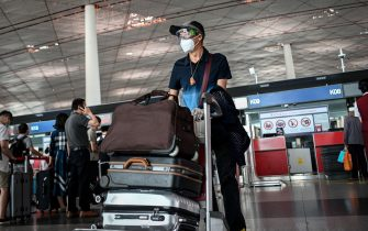 A man wearing a face mask and goggles pushes his luggage at Beijing's international airport on June 17, 2020. - Beijing's airports cancelled more than 1,200 flights and schools in the Chinese capital were closed again on June 17 as authorities rushed to contain a new coronavirus outbreak linked to a wholesale food market. (Photo by STR / AFP) (Photo by STR/AFP via Getty Images)