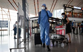 A man wearing a protective suit uses his phone at Beijing's international airport on June 17, 2020. - Beijing's airports cancelled more than 1,200 flights and schools in the Chinese capital were closed again on June 17 as authorities rushed to contain a new coronavirus outbreak linked to a wholesale food market. (Photo by STR / AFP) (Photo by STR/AFP via Getty Images)