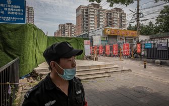epa08487696 A security person wearing a face mask stands guard at the entrance to the Yuquandong market, in Beijing, China, 16 June 2020. Authorities closed the Yuquandong market in the Haidian district, as coronavirus cases had allegedly spread there. Multiple residential compounds near the market were put under the lock down. According to Chinese health authorities, more SARS-CoV-2 and COVID-19 cases have been confirmed in Beijing.  EPA/ROMAN PILIPEY