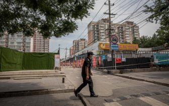 epa08487695 A security person wearing a face mask stands guard at the entrance to the Yuquandong market, in Beijing, China, 16 June 2020. Authorities closed the Yuquandong market in the Haidian district, as coronavirus cases had allegedly spread there. Multiple residential compounds near the market were put under the lock down. According to Chinese health authorities, more SARS-CoV-2 and COVID-19 cases have been confirmed in Beijing.  EPA/ROMAN PILIPEY