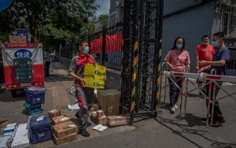 epa08487717 A delivery man delivers packages for residents at a sealed off residential compound near the Yuquandong market, in Haidian district, Beijing, China, 16 June 2020. Authorities closed the Yuquandong market in the Haidian district, as coronavirus cases were spread there and multiple residential compounds near the market were put under the lock down. According to Chinese health authorities, more SARS-CoV-2 and COVID-19 cases have been confirmed in Beijing.  EPA/ROMAN PILIPEY
