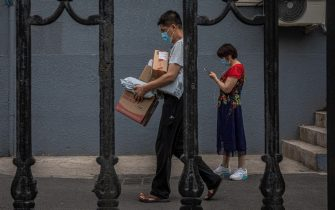 epa08487714 A man wearing a face mask walks with packages at a sealed off residential compound near the Yuquandong market, in Haidian district, Beijing, China, 16 June 2020. Authorities closed the Yuquandong market in the Haidian district, as coronavirus cases were spread there and multiple residential compounds near the market were put under the lock down. According to Chinese health authorities, more SARS-CoV-2 and COVID-19 cases have been confirmed in Beijing.  EPA/ROMAN PILIPEY