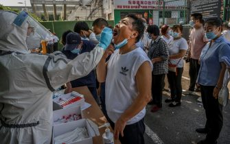 BEIJING, CHINA - JUNE 16: A Chinese epidemic control worker wears a protective suit and mask while performing a nucleic acid test for COVID-19 on a man who has had contact with the Xinfadi Wholesale Market or someone who has, at a testing center on June 16, 2020 in Beijing, China. Authorities are trying to contain the outbreak linked to the Xinfadi wholesale food market, Beijing's biggest supplier of produce and meat. Several neighborhoods have been locked down and at least two other food markets were closed, as tens of thousands of people are being urged to get tested for COVID-19 at sites set up around the city. The outbreak has triggered fears of a second wave of infection after 56 straight days with no domestically transmitted cases in the capital. More than 8,000 vendors and staff at Xinfadi have already been tested, according to city officials, who are using contact tracing to reach an estimated 200,000 people who have visited the market since May 30. (Photo by Kevin Frayer/Getty Images)